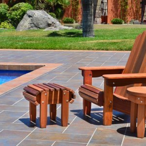 Adirondack Flat Ottoman (Options: Old-Growth Redwood, Transparent Premium Sealant). Photo also shows Adirondack Folding Chairs and Round Side Table.