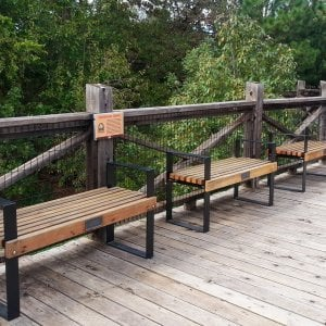 The Alameda Bench (Options: 4 ft, California Redwood, No Cushion, No Engraving, Custom Plaque, Semi-Transparent Stain). Comment: Photo Courtesy of the Oklahoma Zoological Society. Finish is faded somewhat because benches have been out in the weather for nearly 2 years.