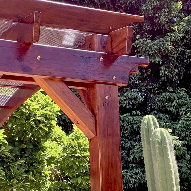 Arched Open Sky Pergola (Options: 12' L x 14' Arc W, California Redwood, 1 Electrical Wiring Trim, 4 Post Anchor Kit for Concrete, No Ceiling Fan Base, No Privacy Panels, No Curtain Rods, 9.5' Post Height, Transparent Premium Sealant). Custom decorative steel shading added by customer. Photo was taken one year after installation. Photo Courtesy of K. Cates of Oajland, California.