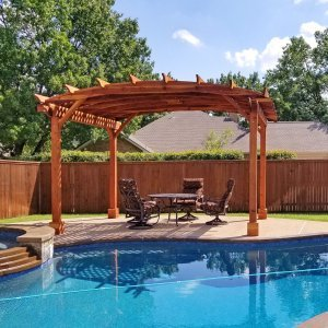 Arched Open Sky Pergola (Options: 12' L x 16' Arc W, Redwood, 1 Electrical Wiring Trim, Horizontal Decorative Trims on Posts, 4 Post Anchor Kit for Concrete, No Ceiling Fan Base, No Privacy Panels, No Curtain Rods, 9' Post Height, Transparent Premium Sealant). Photo Courtesy of T. Heatherly of Coppell, Texas.