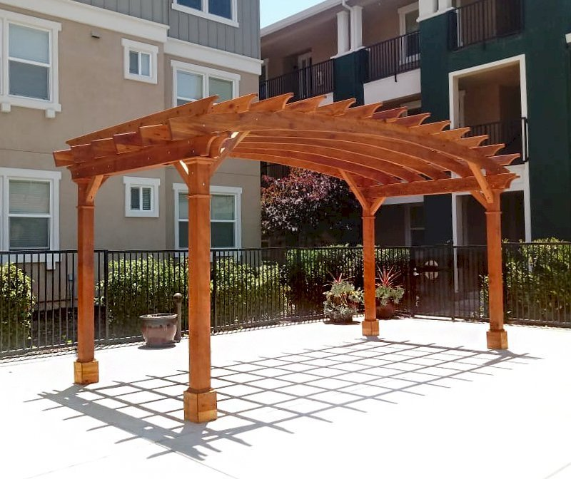 Arched Open Sky Pergola (Options: 10' L x 20' Arc W, California Redwood, No Electrical Wiring Trim, Horizontal Decorative Trims on Posts, 4 Post Anchor Kit for Concrete, No Ceiling Fan Base, No Privacy Panels, No Curtain Rods, 9' Post Height, Transparent Premium Sealant). Photo Courtesy of M. Castaneda of Pleasanton, CA.