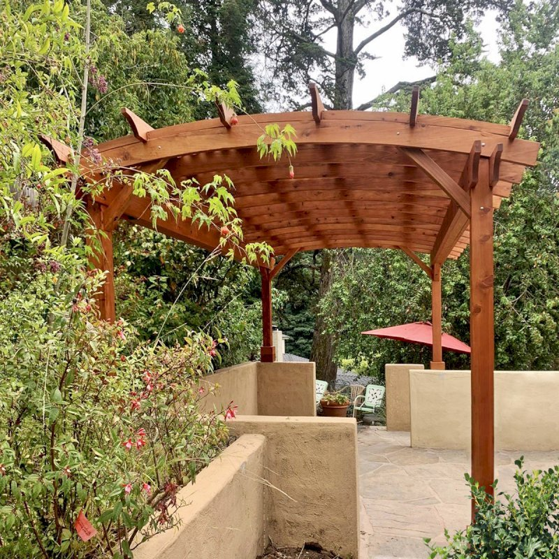 Arched Pergola Kit (Options: 20' L x 12' Arc W, Mature Redwood, No Electrical Wiring Trim Kits, 4 Post Anchor Kit for Concrete, No Ceiling Fan Bases, No Privacy Panels, No Curtain Rods, 9.5' Post Height, Transparent Premium Sealant). Photo Courtesy of L. Nelson of Oakland, CA.