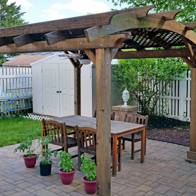 Arched Pergola Kit (Options: 14' L x 12' Arc W, California Redwood, No Electrical Wiring Trim Kit, 4 Post Anchor Kit for Concrete, No Ceiling Fan Base, No Privacy Panels, No Curtain Rods, 9' Post Height, Transparent Premium Sealant). Photo Courtesy of Joe Cario of Moonachie, New Jersey.