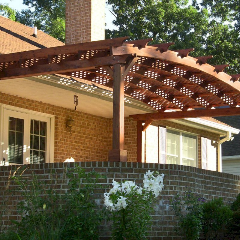 Arched Pergola Kits (Options: 10' L x 22' Arc W, Mature Redwood, Unattached, No Electrical Wiring Trim, Arched Roof with Lattice Panels, 4 Post Anchor kit for Stone, No Ceiling Fan Base, No Privacy Panels, No Curtain Rods, 9' Post Height (Front Posts Shorter by Custom Request), Cherry Stain Premium Sealant). Photo Courtesy of Josef M. of Fayetteville, Pennsylvania.