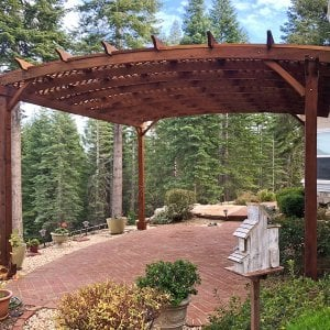 Arched Pergola Kits (Options: 20' L x 18' Arc W, Mature Redwood, Unattached, No Electrical Wiring Trim, Arched Roof with Lattice Panels, 4 Post Anchor Kit for Stone, No ceiling Fan Base, No Privacy Panels, No Curtain Rods, 10' Post Height, Transparent Premium Sealant). Photo Courtesy of Edward G. of Nevada City, CA. The original fotos for this pergola were from 2012. This photo was taken in Dec 2017 after the pergola was refinished by the Forever Redwood crew by request.