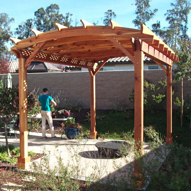 """Arched Pergola Kit. (Options: 16' L x 12' Arc W, California Redwood, No Electrical Wiring Trims, Arched Roof with Lattice Panels, 4 Post Anchor Kit for Concrete, No Ceiling Fan Base, No Privacy Panels, No Curtain Rods, 6"""" Overhangs on Supports Side by Custom Request, Transparent Premium Sealant). Photo Courtesy of Fred Swendson."""