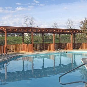 Arched Pergola Kits (Options: 40' L x 14' Arc W, Redwood, No Electrical Wiring Trim, Arched Roof with Lattice Panels, 10 Post Anchor Kit for Wood, 2 Ceiling Fan Bases, No Curtain Rods, Transparent Premium Sealant). Privacy stalls added by custom request. Photo Courtesy of D. Hatcher of Lewis Center, OH.