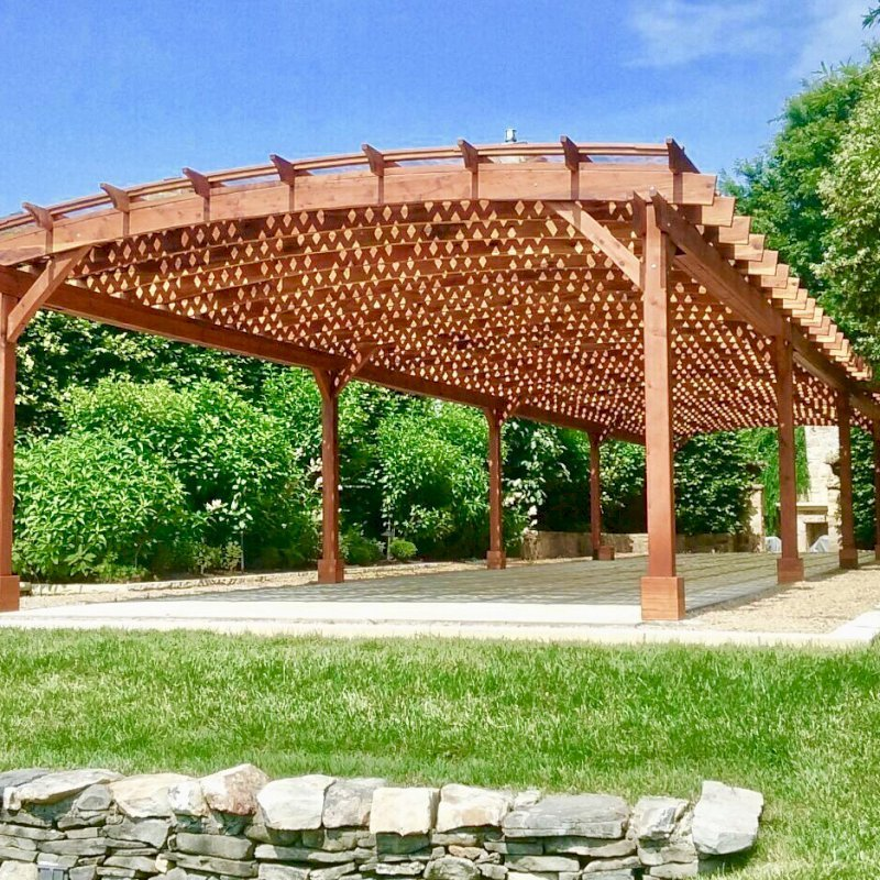 Arched Pergola Kit (Options: 74' L x 18.5' Arc W, Mature Redwood, Electrical Wiring Trim for 1 Post, 10 Post Anchor Kit for Concrete, 2 Ceiling Fan Bases, No Privacy Panels, No Curtain Rods, 9' Post Height, Transparent Premium Sealant). Acrylic Sheets Atop the Roof with Trims and Channels to Drain Water. Photo Courtesy of H. Mitchell of The Plains, VA.