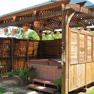 Arched Pergola Kits (Options: 16' L x 14' Arc W, Redwood, Unattached, 2 Post Electrical Wiring Trim, Arched Roof with Lattice Panels, 4 Post Anchor Kit for Stone, No Ceiling Fan Base, 3 Shutter Privacy Panels half height with Wall [Custom Lexan Roofing for Additional Privacy and Water Protection. If you are interested in either of these custom details, let us know.], No Curtain Rods, 9' Post Height,Transparent Premium Sealant. Photo courtesy of Ms. Debbie C, Costa Mesa, CA.