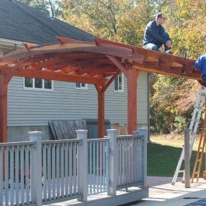 Arched Pergola Kits (Options: 16' L x 12' Arc W, Redwood, Unattached, No Electrical Wiring Trim, Arched Roof with Lattice Panels, 4 Post Anchor Kit for Stone, Ceiling Fan Base, No Privacy Panels, No Curtain Rods, 9' Post Height, Transparent Premium Sealant). Photo Courtesy of Mr John & Virginia Mitchell of Greenwood, Delaware.