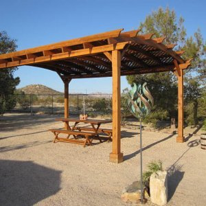 Arched Pergola Kits (Options: 20' L x 15' Arc W , Redwood, Unattached, No Electrical Wiring Trim, Arched Roof with Lattice Panels, 4 Post Anchor Kit for Stone, No Ceiling Fan Base, No Privacy Panels, No Curtain Rods, 9' Post Height, Transparent Premium Sealant). Photo Courtesy of Christine Kelley of Twentynine Palms, CA