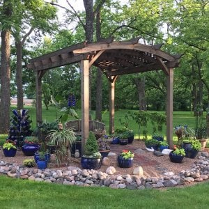 Arched Pergola Kits (Options: 12' L x 14' Arc W, Redwood, Unattached, Electrical Wiring Trim for 1 Post, Arched Roof with Lattice Panels, 4 Post Anchor Kit for Concrete, No Ceiling Fan Base, No Privacy Panels, No Curtain Rods, 9' Post Height, Transparent Premium Sealant). Photo Also Shows a Jane's Key West Chair Under the Pergola. Photo Courtesy of  Kay Taylor of Verona, Wisconsin.