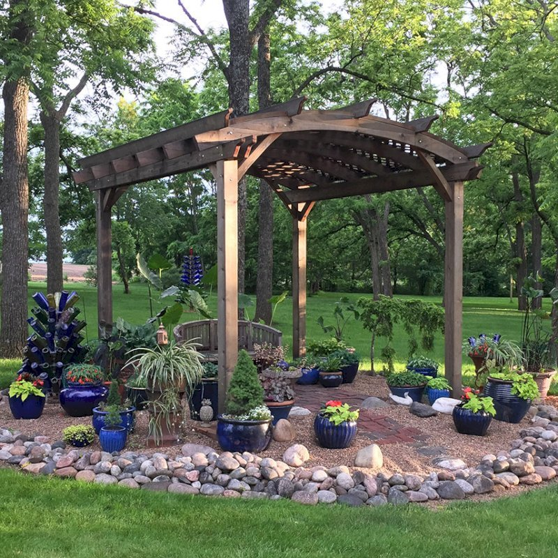 Arched Pergola Kits (Options: 12' L x 14' Arc W, California Redwood, Unattached, Electrical Wiring Trim for 1 Post, Arched Roof with Lattice Panels, 4 Post Anchor Kit for Concrete, No Ceiling Fan Base, No Privacy Panels, No Curtain Rods, 9' Post Height, Transparent Premium Sealant). Photo Also Shows a Jane's Key West Chair Under the Pergola. Photo Courtesy of  Kay Taylor of Verona, Wisconsin.