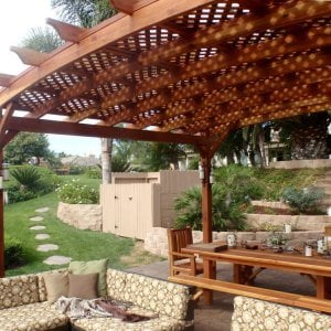 Arched Pergola Kits (Options: 16' L x 20' Arc W, Redwood, Unattached, No Electrical Wiring Trim, Arched Roof with Lattice Panels, 4 Post Anchor Kit for Stone, No Ceiling Fan Base, No Privacy Panel, No curtain Rods, 9' Post Height, Transparent Premium Sealant). 12' Patio Table w/Benches & Ruth Chairs Also Shown. Photo courtesy of Mr. M. Tomacelli of Fallbrook, CA.