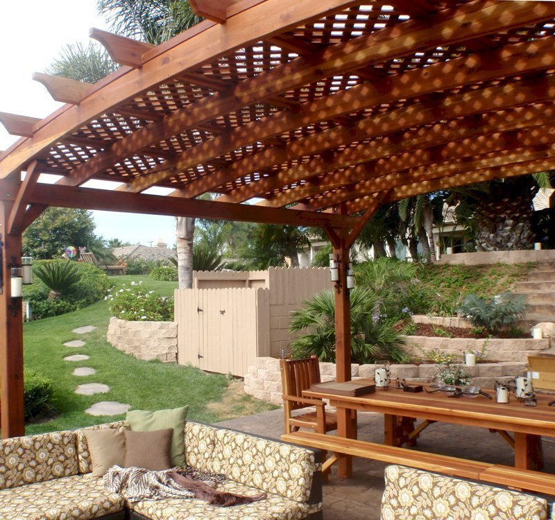 Arched Pergola Kits (Options: 16' L x 20' Arc W, California Redwood, Unattached, No Electrical Wiring Trim, Arched Roof with Lattice Panels, 4 Post Anchor Kit for Stone, No Ceiling Fan Base, No Privacy Panel, No curtain Rods, 9' Post Height, Transparent Premium Sealant). 12' Patio Table w/Benches & Ruth Chairs Also Shown. Photo courtesy of Mr. M. Tomacelli of Fallbrook, CA.