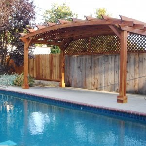 Arched Pergola Kits (Options: 10' L x 20' Arc W, Redwood, Unattached, No Electrical Wiring Trim, Arched Roof with Lattice Panels, 4 Post Anchor Kit for Stone, No Ceiling Fan Base, 1 Privacy Panel, No Curtains Rods, 9' Post Height, Transparent Premium Sealant).