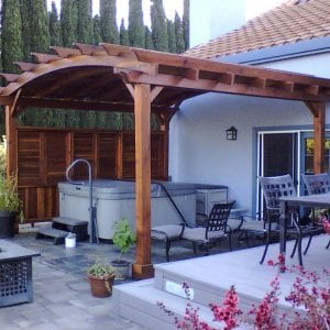 Arched Pergola Kits (Options: 15' L x 16' Arc W, Redwood, Unattached, Electrical Wiring Trim for 1 Post, Arched Roof with Lattice Panels, 4 Post Anchor Kit for Stone, No Ceiling Fan Base, 1 Shutter Privacy Panel half height with wall, No Curtain Rods, 9' Post Height, Transparent Premium Sealant). Photo Courtesy of James Nimmo of Vacaville, CA.