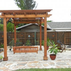 Arched Pergola Kits (Options: 10' L x 12' Arc W, Mature Redwood, Unattached, No Electrical Wiring Trim, Arched Roof with Lattice Panels, 4 Post Anchor Kit for Stone, No ceiling Fan Base, No Privacy Panels, No Curtain Rods, 10' Post Height, Transparent Premium Sealant) with Custom Swing. Photo Courtesy of Sherrie and Jim Kitterman of Dunedin, Florida.
