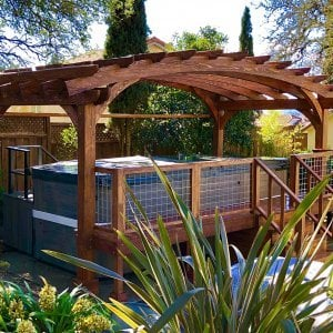 Custom Arched Pergola Kit (Options: 12' L x 22' Arc W, Douglas-fir, Unattached, Electrical Wiring Trim Kit for 1 Post, Arched Roof with Lattice Panels and Acrylic Sheets Centered, 4 Post Anchor Kit for Stone, No Ceiling Fan Base, No Privacy Panels, No Curtain Rods, 9' Post Height, Coffee-Stain Premium Sealant) with Custom Deck and Stairs by Custom Request. Photo Courtesy of Steve & Heidi Jones of Windsor, CA.