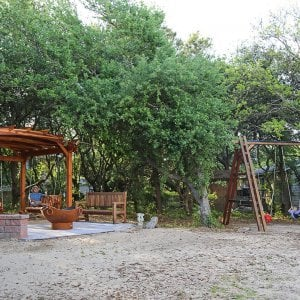 Arched Pergola Kits (Options: 12' L x 14' Arc W, Redwood, Unattached, Electrical Wiring Trim for 1 Post, Arched Roof with Lattice Panels, 4 Post Anchor Kit for Gale-Wind, No Ceiling Fan Base, No Privacy Panels, No Curtain Rods, 9' Post Height, Transparent Premium Sealant). With 2 Bench Swings by Custom Request. Photo Also Shows a Rory's Swing Set and a Ti Amo Bench. Photo Courtesy of Tom Marten of Kitty Hawk, North Carolina.