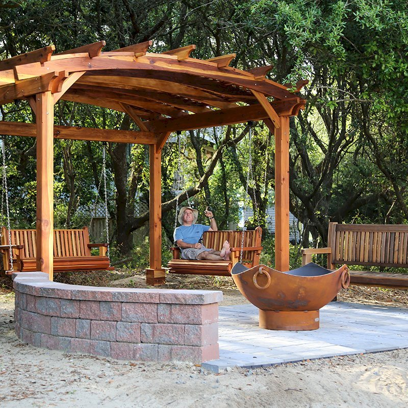 Arched Pergola Kits (Options: 12' L x 14' Arc W, California Redwood, Unattached, Electrical Wiring Trim for 1 Post, Arched Roof with Lattice Panels, 4 Post Anchor Kit for Gale-Wind, No Ceiling Fan Base, No Privacy Panels, No Curtain Rods, 9' Post Height, Transparent Premium Sealant). With 2 Bench Swings by Custom Request. Photo Also Shows a Ti Amo Bench. Photo Courtesy of Tom Marten of Kitty Hawk, North Carolina.