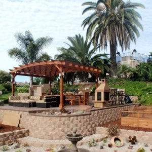 Arched Pergola Kits (Options: 14' L x 18' Arc W, Redwood, Attached,  No Electrical Wiring Trim, Arched Roof with Lattice Panels, 4 Post Anchor Kit for Stone, No Ceiling Fan Base, No Privacy Panel, No Curtain Rods, 9' Post Height, Transparent Premium Sealant).  Posts wrapped in masonry. Photo courtesy of Mr. Brandon Campbell of  Lenoir City, TN.