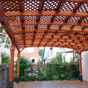 Arched Pergola Kits (Options: 25' L x 20' Arc W, Redwood, Unattached, No Electrical Wiring Trim, Arched Roof with Lattice Panels, 6 Post Anchor Kit for Stone, with Ceiling Fan Base, No Privacy Panels, No Curtain Rods, Transparent Premium Sealant). Note: Photo shows roof detail of pergola still under construction (note trim kit boxes set near top of posts and plastic wrap around anchoring hardware at base of posts). Photo Courtesy of Mr. Ami Liani of Brooklyn, NY.
