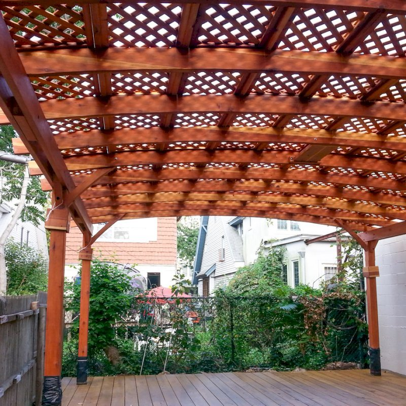 Arched Pergola Kits (Options: 25' L x 20' Arc W, California Redwood, Unattached, No Electrical Wiring Trim, Arched Roof with Lattice Panels, 6 Post Anchor Kit for Stone, with Ceiling Fan Base, No Privacy Panels, No Curtain Rods, Transparent Premium Sealant). Note: Photo shows roof detail of pergola still under construction (note trim kit boxes set near top of posts and plastic wrap around anchoring hardware at base of posts). Photo Courtesy of Mr. Ami Liani of Brooklyn, NY.