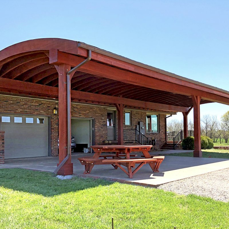 Custom Arched Thick Timber Pavilion (Options: 55' L x 22' Arc W, California Redwood, No Electrical Wiring Trim, 6 Post Anchor Kit for Gale-Wind, 2 Ceiling Fan Bases, No Privacy Panel, No Curtain Rods, 10ft H, Cherry Stain Premium Sealant) Support timbers covered by custom request. Photo also shows a Round Picnic Table. Photo Courtesy of J. Hartmann of Pittsburg, KS.