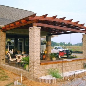 Attached Arched Pergola (Options: 14' L x 18' W, California Redwood, No Electrical Wiring Trim, Arched Roof with Lattice Panels, 2-Post Kit for Concrete, No Ceiling Fan Base, No Privacy Panels, No Curtain Rods, 9' Post Height,  Transparent Premium Sealant).  Posts wrapped in masonry. Photo courtesy of Mr. Brandon Campbell of  Lenoir City, Tennessee.