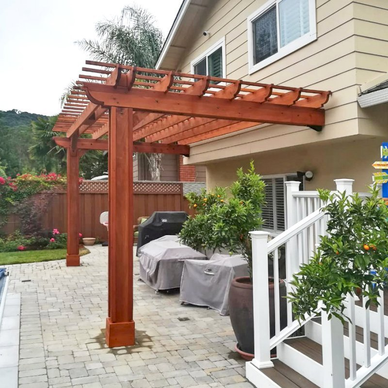 "Attached Garden Pergola (Options: 20' L x 10' W, Mature Redwood, No Electrical Wiring Trim, 2-post anchor kit for gale-wind, Open Roof with Slats at 12"", Rafters at 18"", Vertical post decorative trim, Transparent Premium Sealant). Photo Courtesy of D. Abrams of San Jose, California."