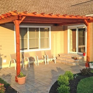 "Attached Garden Pergola (Options: 12' x 18', Attached to Wall by Rafters Side, California Redwood, No Electrical Wiring Trim, Open Roof with Slats at 18"", Transparent Premium Sealant)."