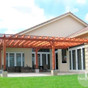 "Attached Garden Pergola (Options: 26' L x 15' W, Attached to Wall by Rafters Side, Mature Redwood, No Electrical Wiring Trim, Open Roof with Slats at 18"", 4-Post Anchor Kit for Concrete, Transparent Premium Sealant)."