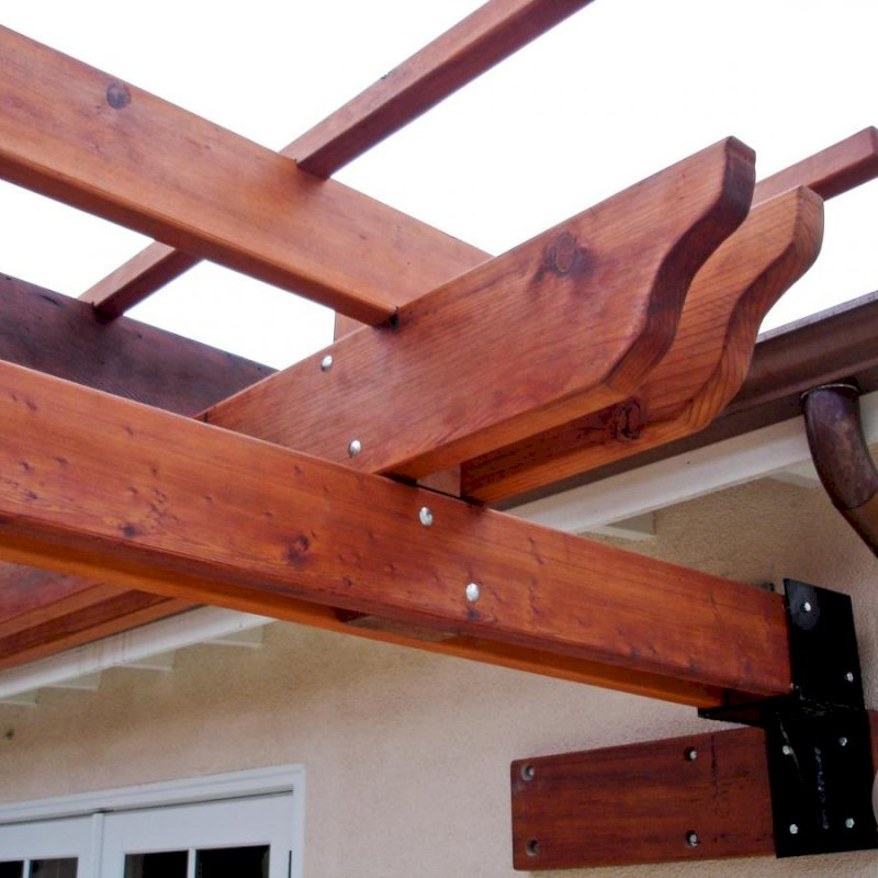 Some attached pergolas cannot be secured with a ledger board. In some instances, we build custom steel anchors to get the job done like shown here. Photo also highlights the extensive notching and finishing work that goes into each timber of our Kits.