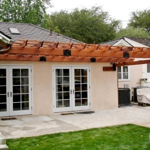 "Attached Garden Pergola (Options:10' L x 14' W, Attached to Wall by 2 Sides by Custom Request, Mature Redwood, No Electrical Wiring Trim, Open Roof with Slats at 18"", 1-Post Anchor Kit for Concrete, Transparent Premium Sealant)."
