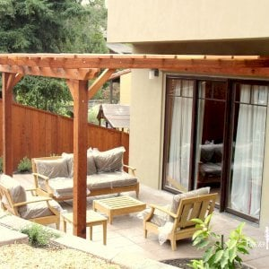 "Attached Garden Pergola (Options: 12' L x 12' W, Attached to Wall by Support Side, Mature Redwood, No Electrical Wiring Trim, Open Roof with Slats at 18"", 2-Post Anchor Kit for Concrete, Transparent Premium Sealant)."