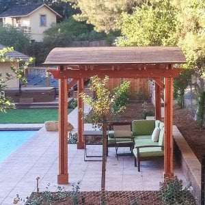 Backyard Pavilion (Options: 10' x 18', Redwood, No Electrical Wiring Trim Kit, 4 Post Anchor Kit for Concrete, No Ceiling Fan Base, No Privacy Panels, No Curtain Rods, 8.5 ft Post Height, Transparent Premium Sealant). Photo Courtesy of Susan Peters of Novato, CA.