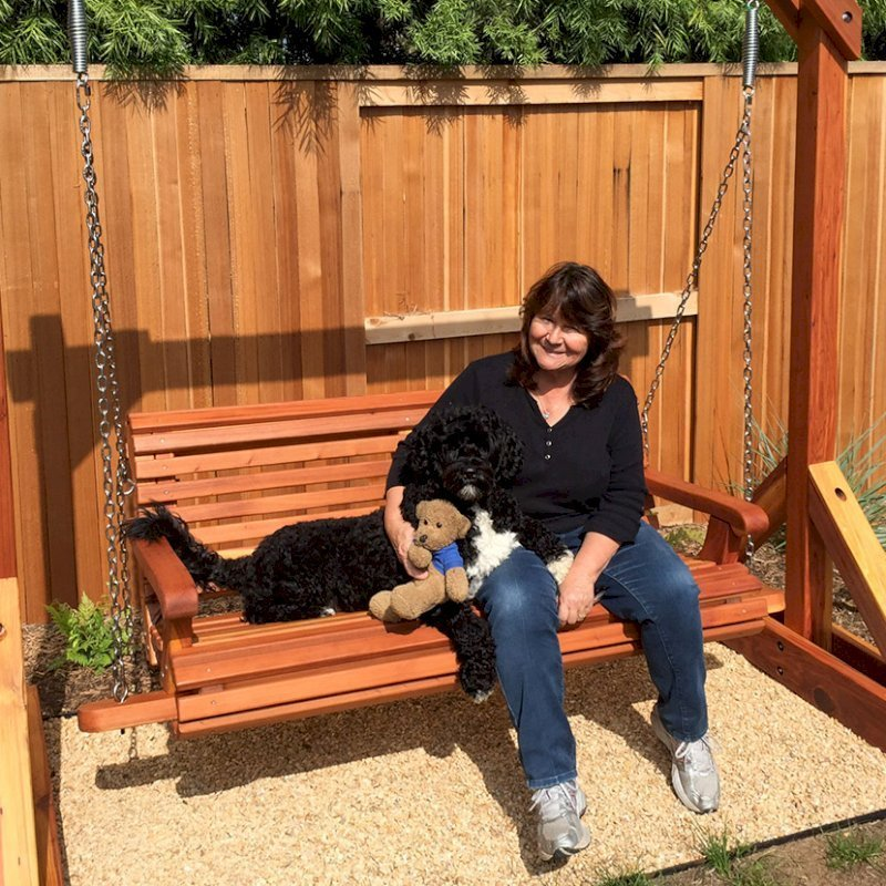Bench Swing Set (Options: Large Bench, No Swing Roof, California Redwood, Ensenada Style Seat, No Engraving, Transparent Premium Sealant).  Photo Courtesy of Mr. Stephen Carlson of Playa Del Rey, CA. The models are Donna Carlson and her portaguise water dog Scupper