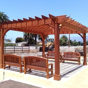 Cherry Hill Pergola (Options: 16' x 20', Mature Redwood, Post Anchoring for Concrete, No Ceiling Fan Base, No Curtain Rods, No Privacy Panels, 9.5' Post, Transparent Premium Sealant). 2 x 8 Roof Timbers and 8 x 8 Posts by Custom Request. Photo also shows 4 Luna Memorial Benches. Photos taken in Carpinteria Garden Park during construction, May 10, 2017. Photo Courtesy of M. Roberts of Carpinteria, CA.