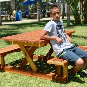 "Chris's Picnic Table (Options: 6' L x 34"" W, Redwood, Standard Tabletop, Rounded Corners, Umbrella Hole, Transparent Premium Sealant)."