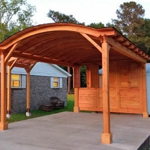 Custom Wood Pavilion Kits (Options: 20' L, 14' W, 1 Shutter Privacy Panel, Douglas-fir, No Electrical Wiring Trim, 2 Post Anchor Kit for Concrete, No Ceiling Fan Base, No Curtain Rods, 9.5' Post Height, Transparent Premium Sealant) with an Attached Arched Pergola on the Left. Photo Courtesy of E.West of Pine Hill, AL.