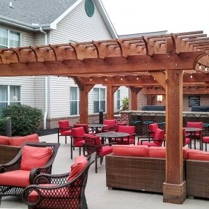 """Custom Wooden Fat Timber Pergola (Options: 20' x 20', Redwood, Electrical Wiring Trim for 1 Post, Open Roof with Rafters at 18"""", Slats at 12"""", 4-Post Anchor Kit for Concrete, No Ceiling Fan Bases, No Privacy Panels, No Curtain Rods, Transparent Premium Sealant). Thicker Lumber by Custom Request, 2 x 12 Rafters & Supports, 10 x10 Posts. Photo Courtesy of Homewood Suites by Hilton, Mechanicsburg, PA."""