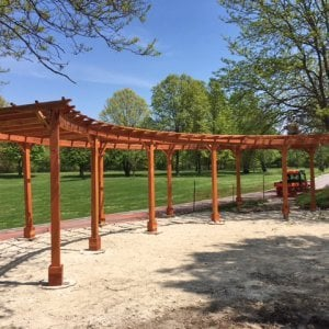 "Custom Fan Shaped Corner Pergola (Options: 50' x 12', Redwood, Open Roof with Slats at 18"", No Electrical Wiring Trim Kit, 12-Post Anchoring for Concrete, No Ceiling Fan Base, 9' Posts, No Curtain Rods, Transparent Premium Sealant). Photo Courtesy of A. Amstutz of Toledo, OH."