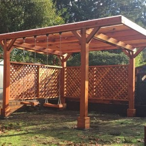 Custom Pergola (Options: 18' x 15', Redwood, No Electrical Wiring Trim, Widthwise Roof Supports TImbers, 4-Post Anchor Kit for Stone, 2 Privacy Panels, No Curtain Rods, Roof with a Slope, Transparent Sealant) with 2 Rory's Swing Seats, Added by Custom Request. Customer Added Lexan Panels. Photo Courtesy of Tina Phi of Palo Alto, CA.