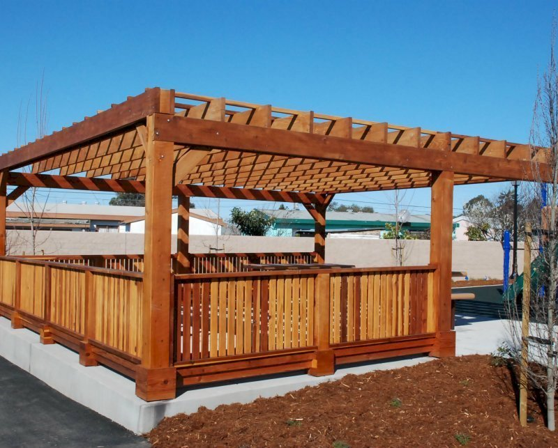 "Custom Pergola (Options: 24' x 24', California Redwood, Open Roof with Slats at 18"", Rafters at 18"", 1¾"" x 9¼"" Supports and Rafters, 8 x 8 Posts, Transparent Premium Sealant). Photo Courtesy of Wanlass Park of San Pablo, CA."