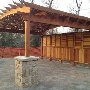 Custom Pergola (Options: 20' x 18', Redwood, No Electrical Wiring Trim, Arched Roof with Lattice Panels, Lengthwise Roof Supports TImbers, 4-Post Anchor Kit for Stone, 4 1 Shutter Privacy Panels half height with wall, No Curtain Rods, Custom Post Size, Transparent Sealant). We can add just about any detail to a Pergola project. Photo Courtesy of Neil E. of St. Louis, MI.