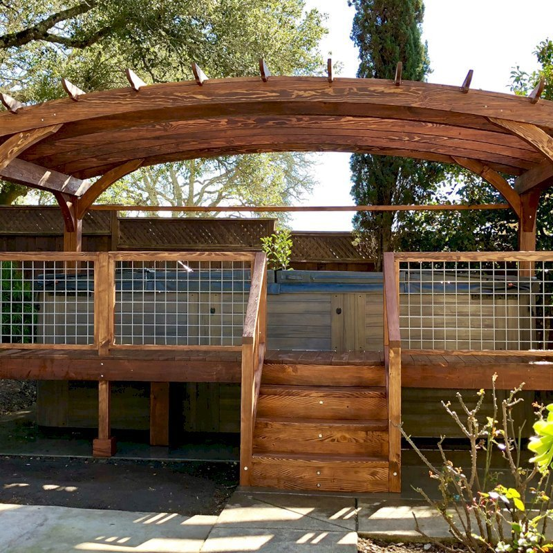 Custom Arched Pergola Kits (Options: 12' L x 22' Arc W, Douglas-fir, Unattached, Electrical Wiring Trim Kit for 1 Post, Arched Roof with Lattice Panels and Acrylic Sheets Centered, 4 Post Anchor Kit for Stone, with 8 x 8 Posts by Custom Request, No Ceiling Fan Base, No Privacy Panels, 1 Curtain Rod, 9' Post Height, Coffee-Stain Premium Sealant) with Custom Deck and Stairs by Custom Request. Photo Courtesy of Steve & Heidi Jones of Windsor, CA.