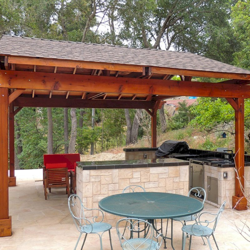 Del Norte Outdoor Kitchen Pavilion (Options: 18' L x 18' W, California Redwood, Unattached, 4 Post Anchor Kit for Stone, Brick or Concrete, No Electrical Wiring, 9 ft Post Height, No Privacy Panels, No Curtain Rods, Transparent Sealant).