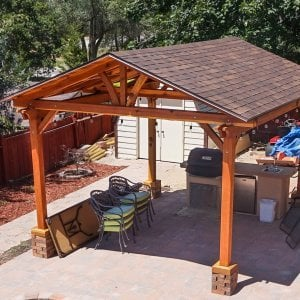 Del Norte Outdoor Kitchen Pavilion (Options: 16' L x 14' W, Redwood [Mature Redwood Posts], Unattached, 4-Post Kit for High Wind, Electrical Wiring Trim for 1 Post, 9.5' Posts, No Ceiling Fan Base, No Privacy Panels, No Curtain Rods, Transparent Premium Sealant). Shingles not Included. Photo Courtesy of K. Hyde of Ogden, Utah.