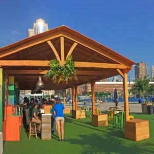 Rio on the Hudson: Olympic Village in NYC. 2 Del Norte Pavilions (Options: 25' L x 20' W, Douglas-fir, We used 2' x 2' x 2'  Concrete Blocks to Anchor the Structure Because it is a Temporary Installation, Covered the Concrete Blocks with Wooden Boxes, No Ceiling Fan Base, Transparent Premium Sealant). Photo Courtesy of A. Fisher of New York, NY.